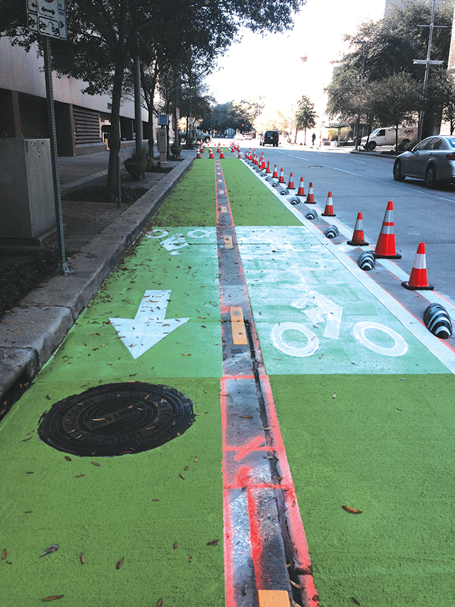 """The Lamar Cycle Track, Houston's first two-way fully protected bike lane. Photo by Laura Hilsmeier, originally published on swamplot.com, Houston's Real Estate Landscape blog. Houston is rapidly becoming a city of cyclists. With a nod toward this trend, the city offers a 345-mile interconnected bikeway network spanning across 500 square miles of the city. The network includes bike lanes, bike routes, shared lanes and bayou trails, rails to trails, and other urban multi-use paths. Recently, swamplot.com updated readers on an important new bikeway, The Lamar Cycle Track, which represents Houston's first two-way fully protected bike lane. """"The track provides a nearly three-quarter-mile connector from Sam Houston Park to Discovery Green, and provides a safe, well-defined path for users between the Buffalo Bayou Trailsand the  Colombia Tap Trail,"""" the blog reported."""